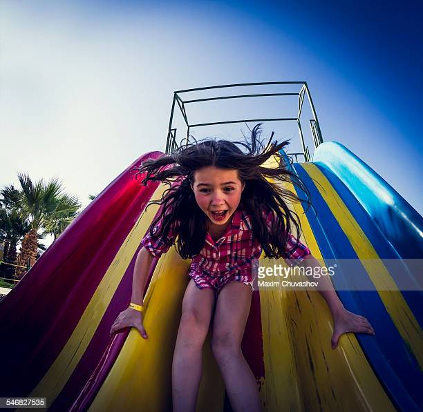 Caucasian girl playing on slide