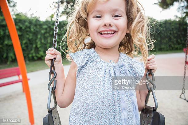 Caucasian girl playing on swing