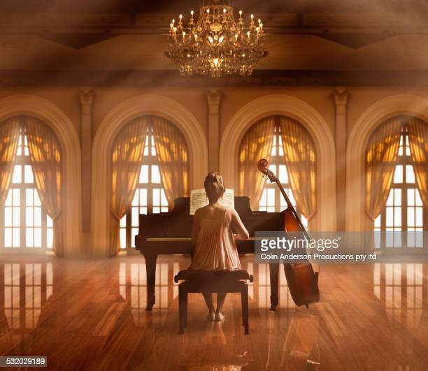 Caucasian girl playing piano in ballroom