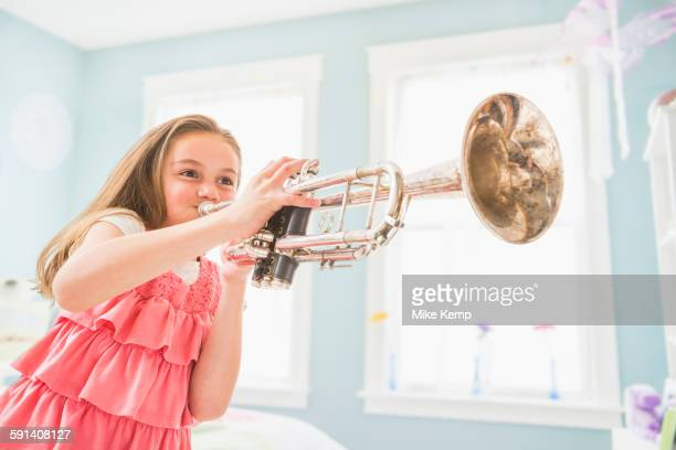 Caucasian girl playing trumpet in bedroom