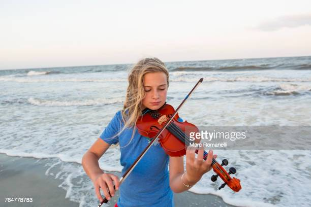 Caucasian girl playing violin at beach