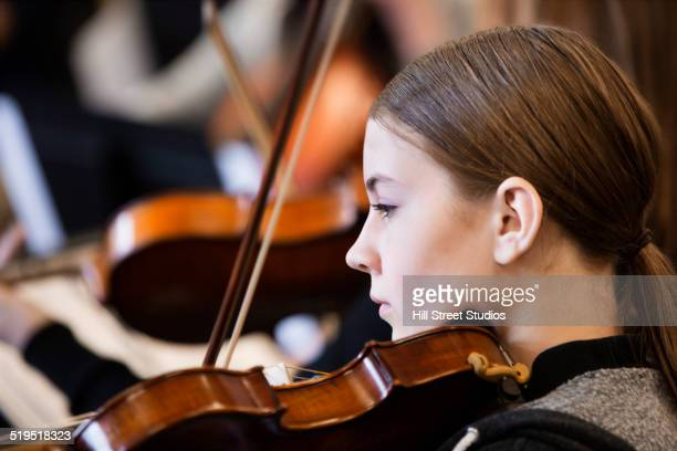 Caucasian girl playing violin in orchestra