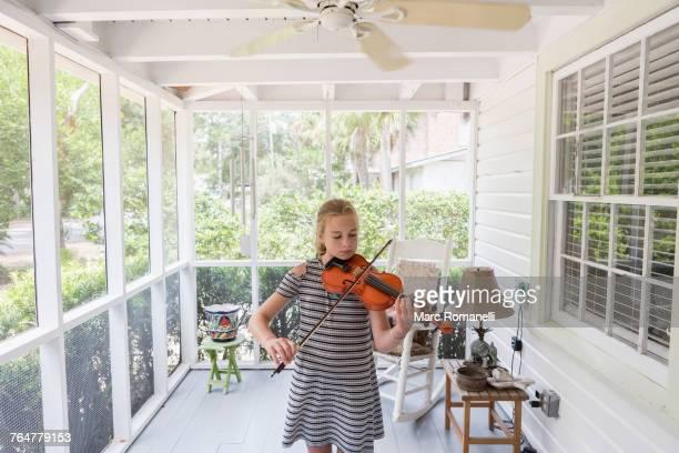Caucasian girl playing violin on patio
