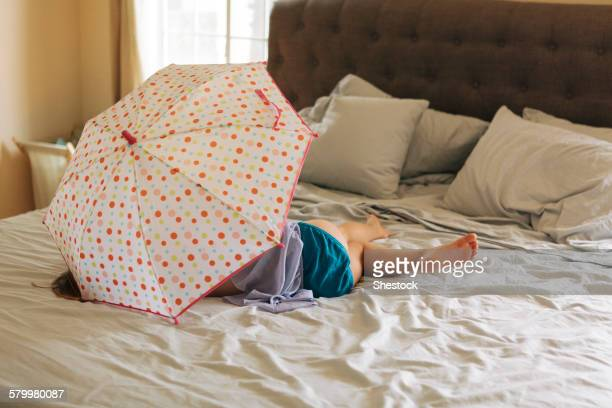 caucasian girl playing with umbrella on bed - petite fille culotte photos et images de collection