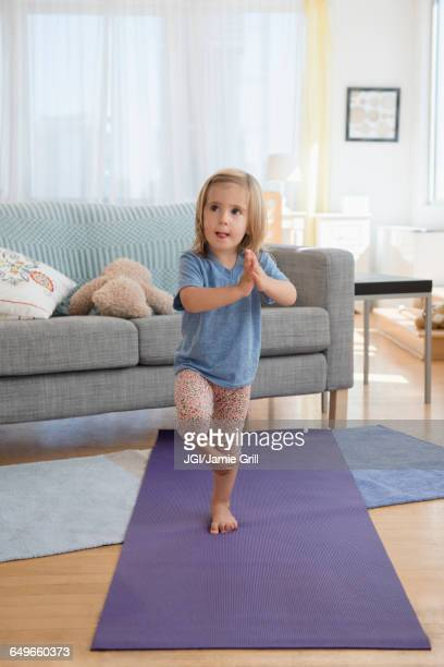 caucasian girl practicing yoga in living room - tree position stock photos and pictures