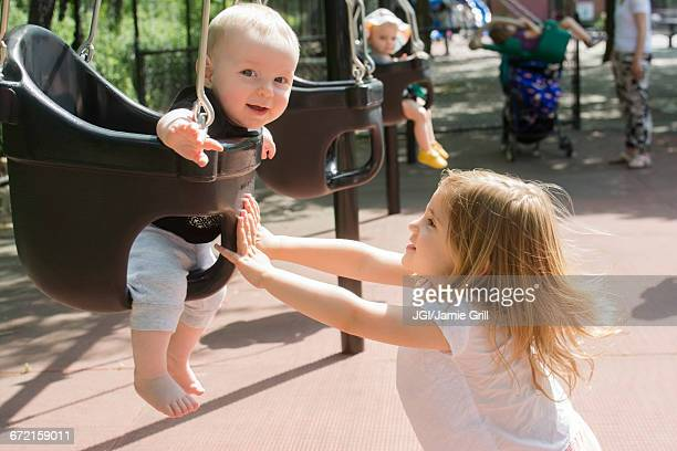 Caucasian girl pushing baby in swing