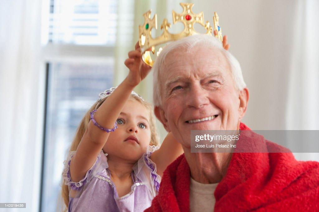 Caucasian girl putting crown on grandfather's head : Stock Photo