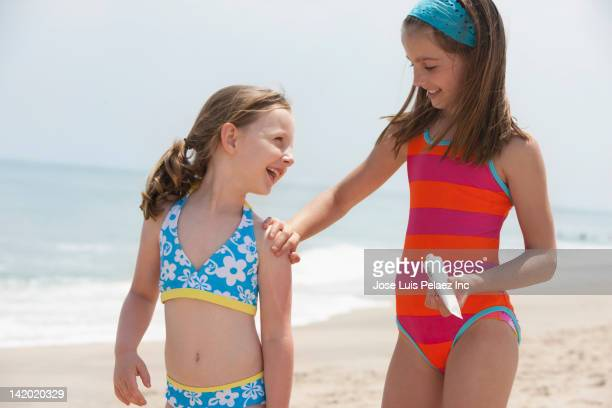 Caucasian girl putting sunscreen on sister