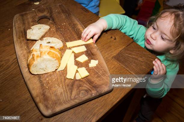 Caucasian girl reaching for cheese near bread on cutting board