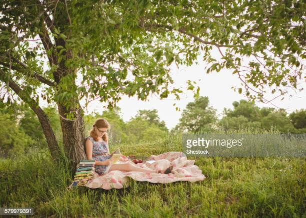 caucasian girl reading book under tree in field - midsommar stock pictures, royalty-free photos & images