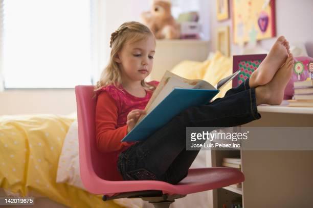 caucasian girl reading book with feet up - blootvoets stockfoto's en -beelden
