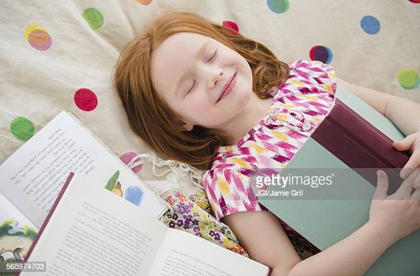 Caucasian girl reading books on bed