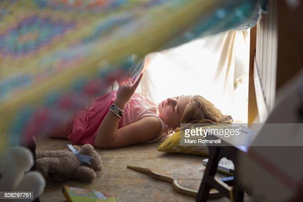 Caucasian girl reading in blanket fort