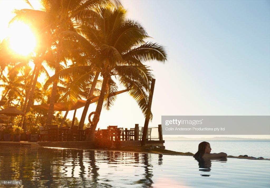 Caucasian girl relaxing in still pool overlooking ocean : Stock-Foto
