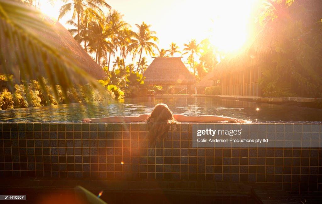Caucasian girl relaxing in swimming pool : Stock Photo