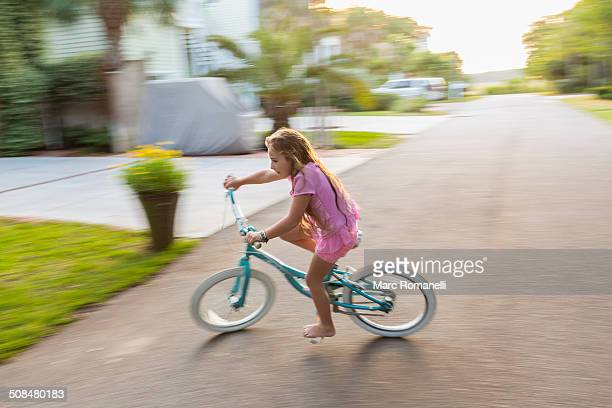 Caucasian girl riding bicycle on street