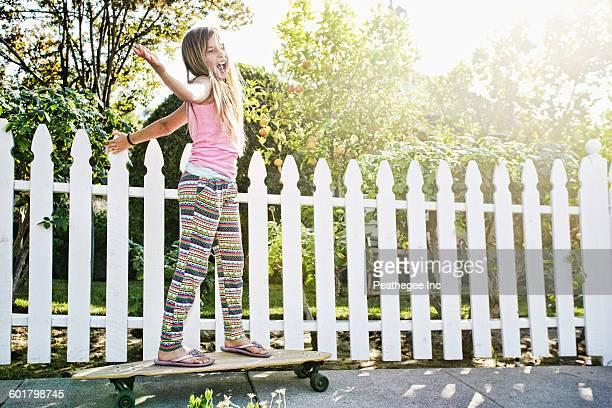 Caucasian girl riding skateboard on sidewalk