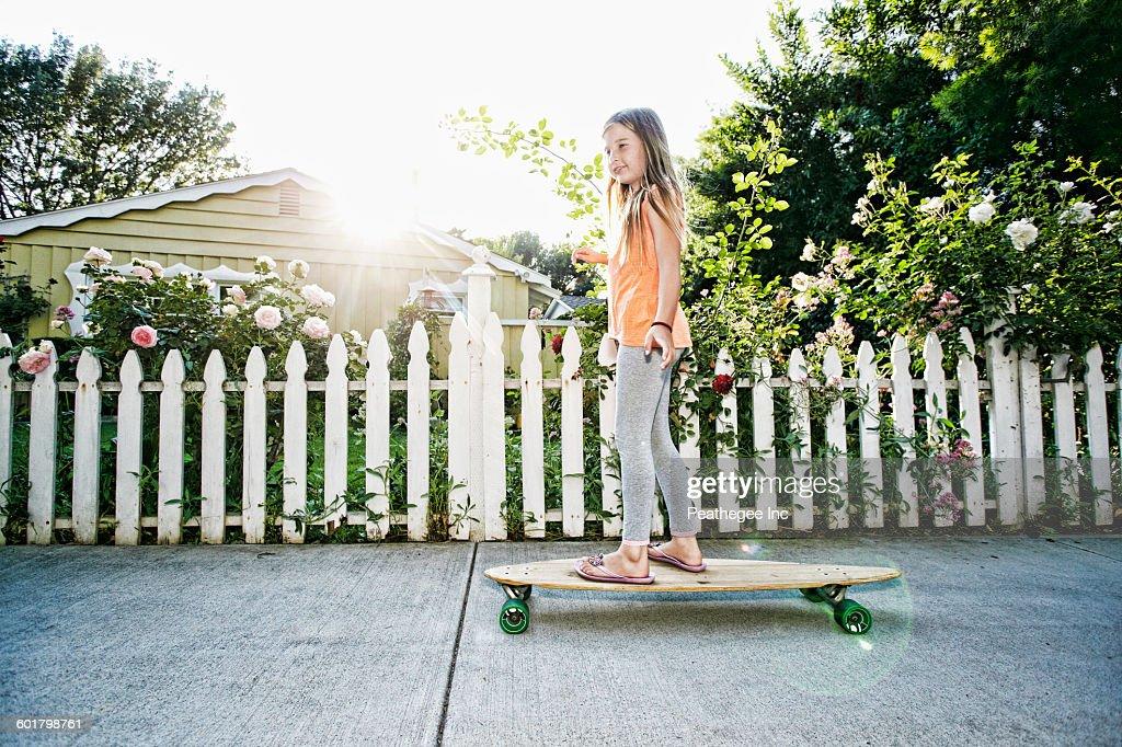 Caucasian girl riding skateboard on sidewalk : ストックフォト