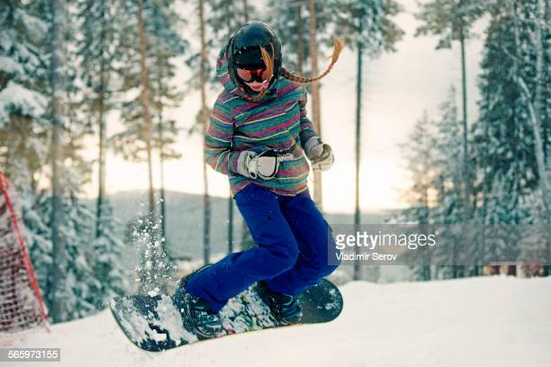 Caucasian girl riding snowboard in snow