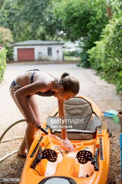 Caucasian girl rinsing kayak with hose