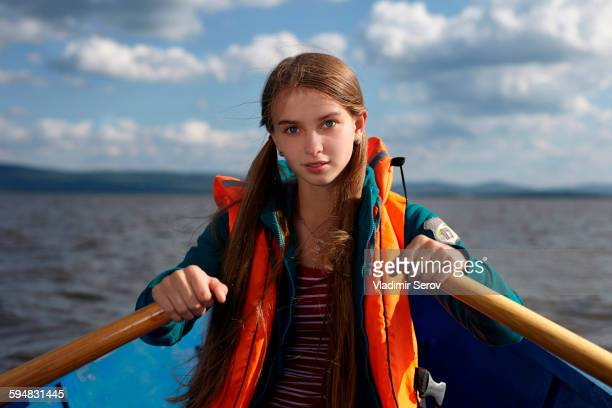 Caucasian girl rowing canoe in lake