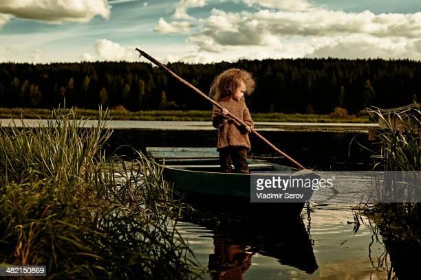 Caucasian girl rowing canoe in still lake