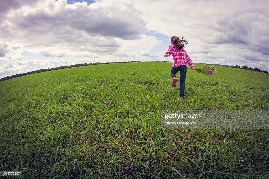 Caucasian girl running in grassy field : Foto stock