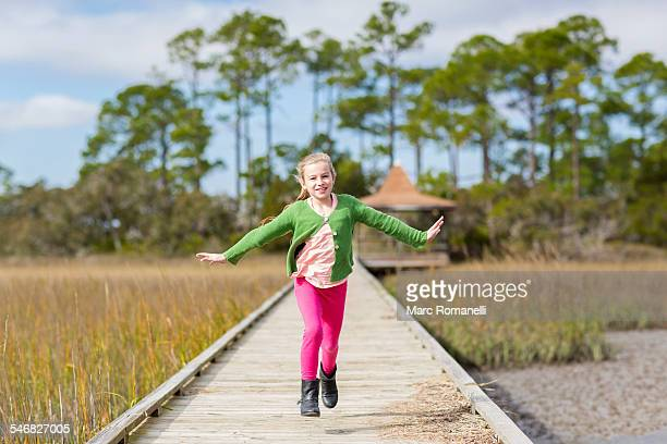 caucasian girl running on wooden walkway - skipping along stock pictures, royalty-free photos & images