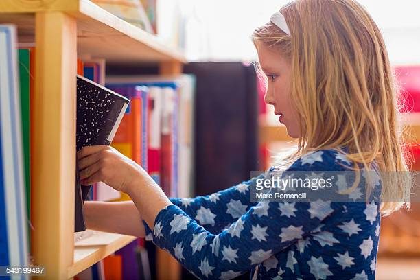 caucasian girl selecting book in library - montessori education stock pictures, royalty-free photos & images