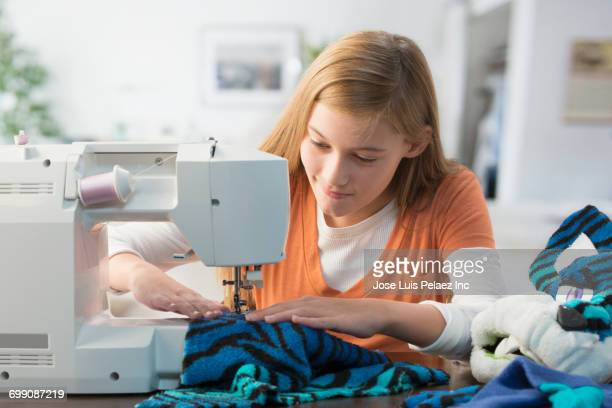 Caucasian girl sewing costume with sewing machine