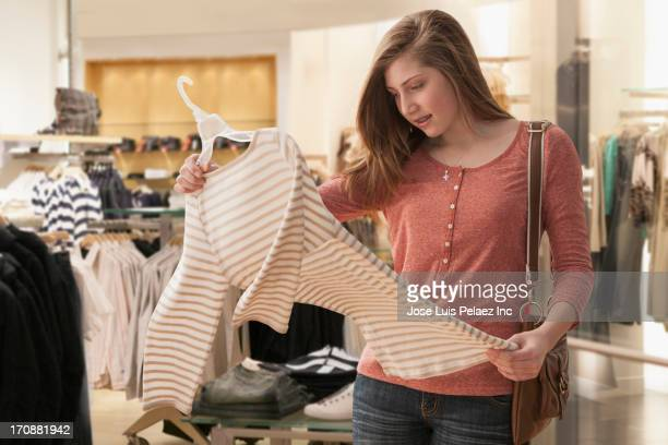 Caucasian girl shopping in clothes store