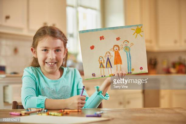Caucasian girl showing drawing of family