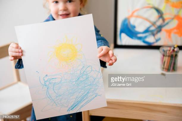 Caucasian girl showing drawing on paper
