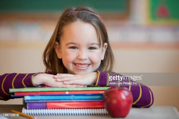 caucasian girl sitting at school desk with books and apple - workbook stock photos and pictures
