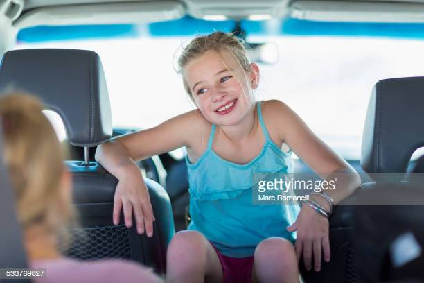 Caucasian girl sitting between seats in car