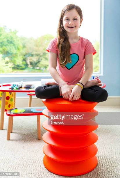 Caucasian girl sitting cross-legged on stool in playroom