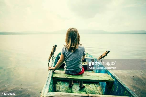 Caucasian girl sitting in boat on still lake