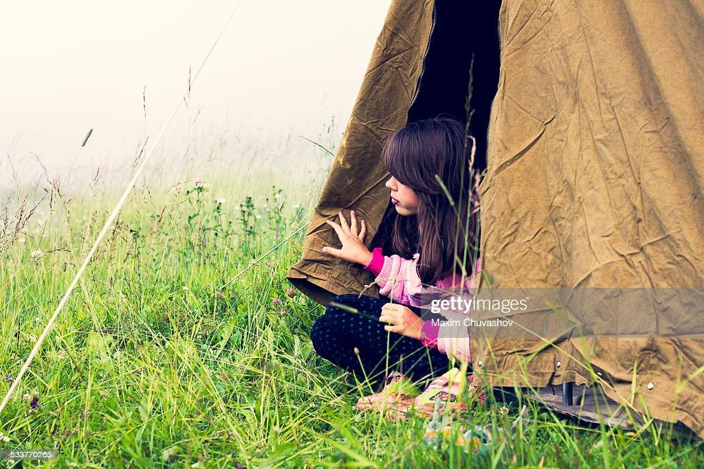 Caucasian girl sitting in camp tent : Foto stock