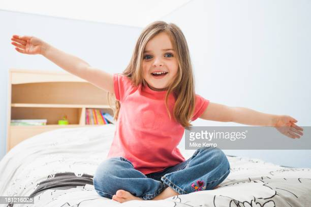 Caucasian girl sitting on bed