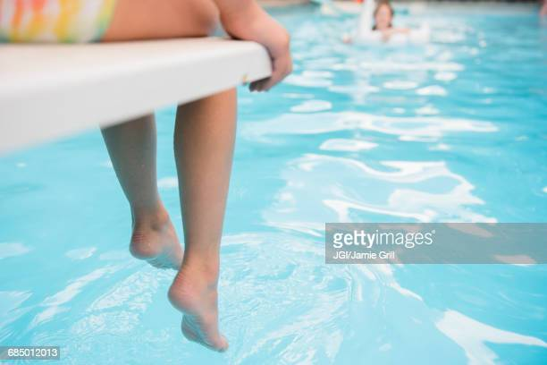Caucasian girl sitting on diving board over swimming pool