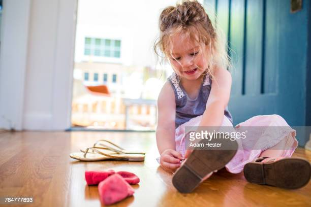 caucasian girl sitting on floor fastening sandal - sandal stock pictures, royalty-free photos & images