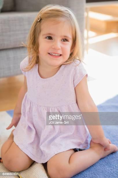 Caucasian girl sitting on floor