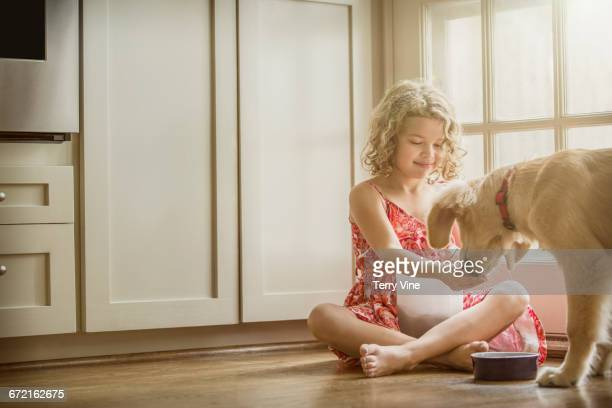 Caucasian girl sitting on kitchen floor feeding dog