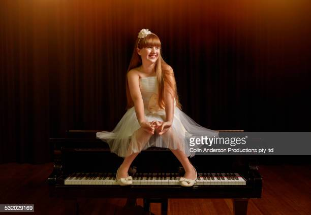 caucasian girl sitting on piano on stage - pianist front stock pictures, royalty-free photos & images