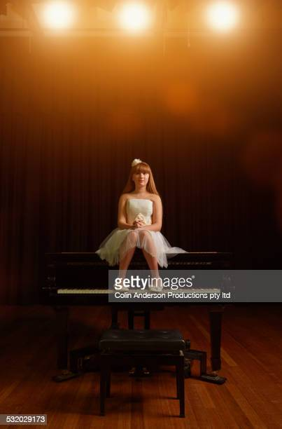 caucasian girl sitting on piano on stage - fabolous musician stock photos and pictures