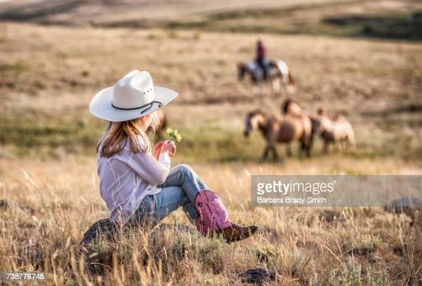 Caucasian girl sitting on rock in field holding flower
