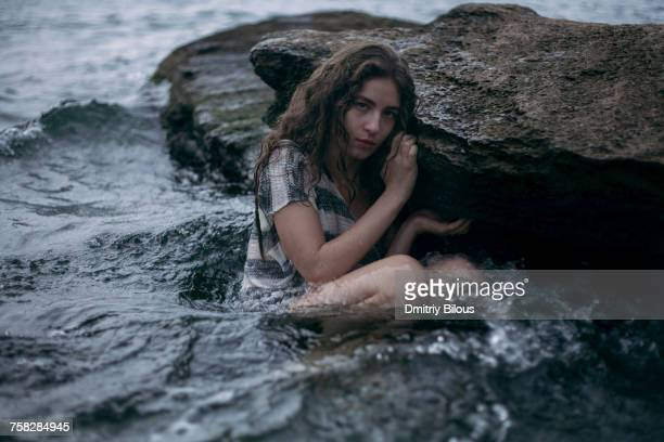 caucasian girl sitting on rock in ocean - waist deep in water stock pictures, royalty-free photos & images