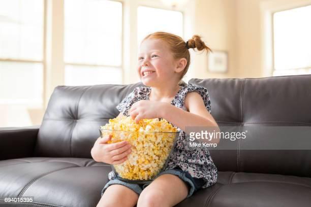 Caucasian girl sitting on sofa eating bowl of popcorn