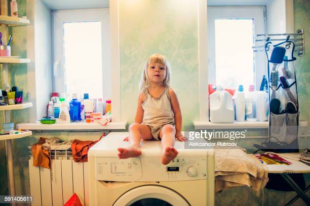 Caucasian girl sitting on washing machine