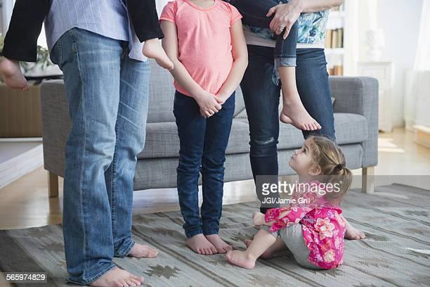 Caucasian girl sitting under family in living room